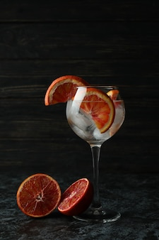 Verre de cocktail au pamplemousse sur table noire smokey