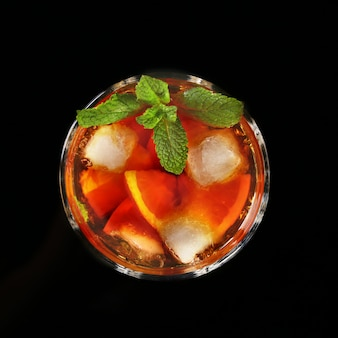Verre de cocktail au rhum foncé avec citron vert, orange, glaçons et feuilles de menthe sur fond de miroir noir.