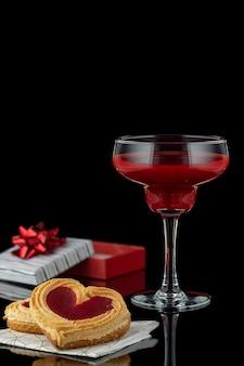 Verre de cocktail aux fraises rouges et biscuits en forme de coeur avec marmelade