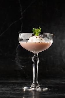 Verre de cocktail baileys glacé servi dans un verre coupé décoré d'une feuille de menthe placée