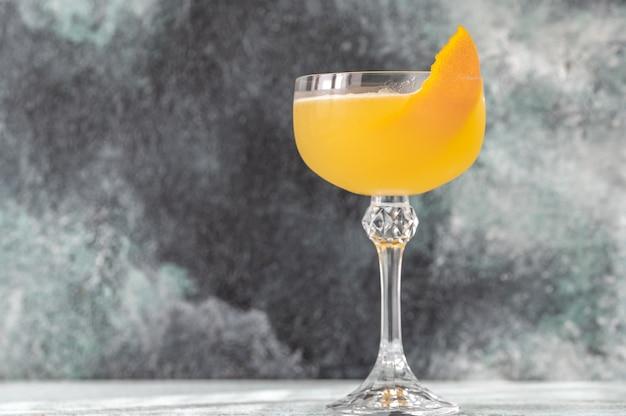Verre de cocktail bee's knees garni de zeste d'orange