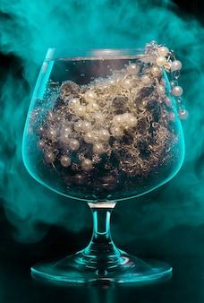 Verre à cocktail de bijoux plein de divers bijoux sur fond noir avec de la fumée