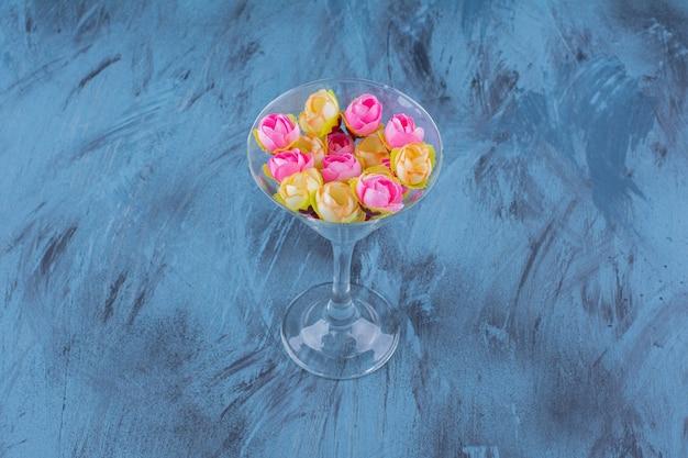 Verre à cocktail avec composition florale colorée sur bleu.