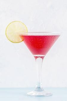 Verre de cocktail cosmopolite décoré de citron vert, mise au point sélective