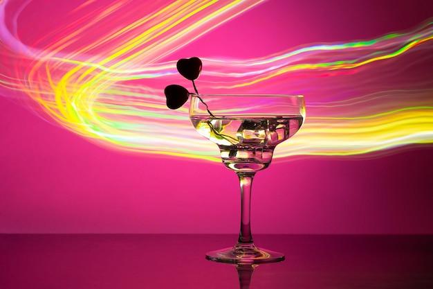 Verre avec un cocktail et deux coeurs.