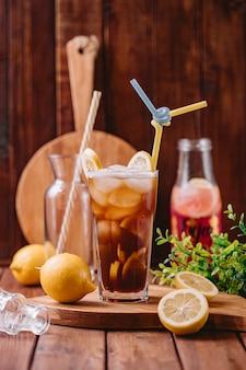 Un verre à cocktail avec du citron et des glaçons et deux pipes en paille en plastique