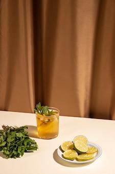 Verre à cocktail avec des feuilles de menthe et des tranches de citron vert sur une table blanche contre un rideau marron