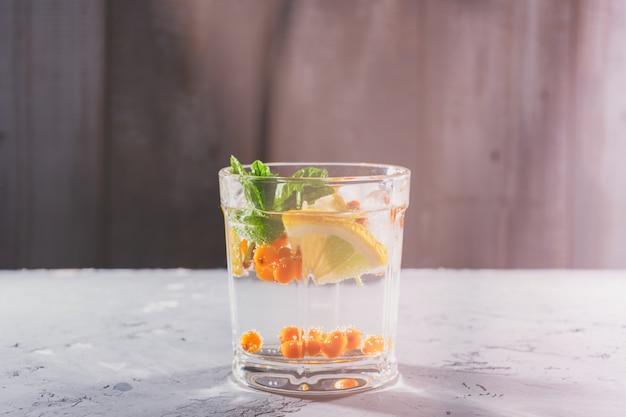 Un verre avec un cocktail de fitness à base d'eau, d'argousier, de citron et de menthe, espace de copie