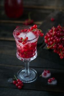 Verre de cocktail de groseille rouge ou mocktail, boisson d'été rafraîchissante avec de la glace pilée et de l'eau pétillante sur une surface en bois sombre