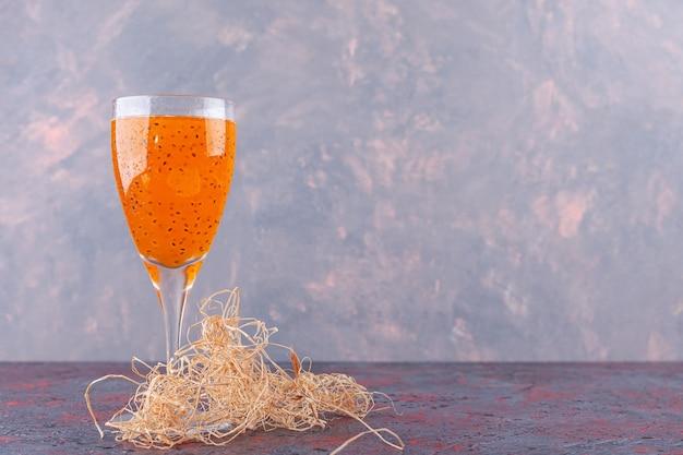 Verre à cocktail de jus de fruits frais aux graines de basilic sur marbre.