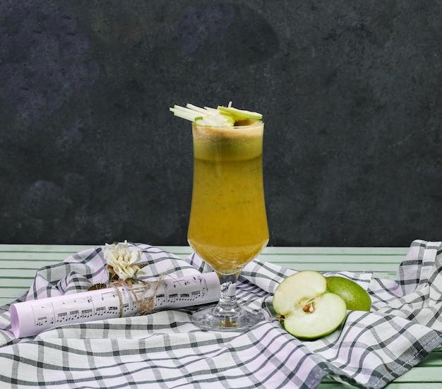 Un verre de cocktail de jus de pomme sur un morceau de bois.