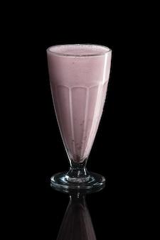 Verre de cocktail de lait framboise isolé sur fond noir