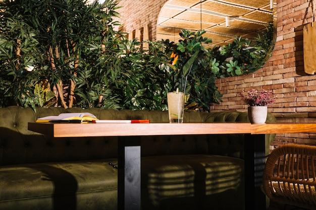 Verre de cocktail; livre; téléphone portable et tablette numérique sur une table en bois dans le restaurant