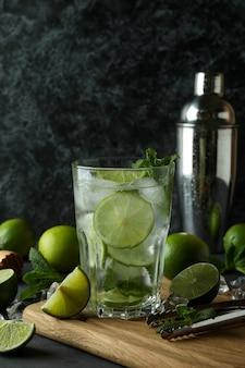 Verre de cocktail mojito et ingrédients sur fond sombre fumé