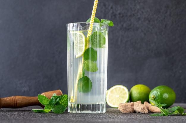 Verre de cocktail mojito avec des ingrédients sur un mur sombre