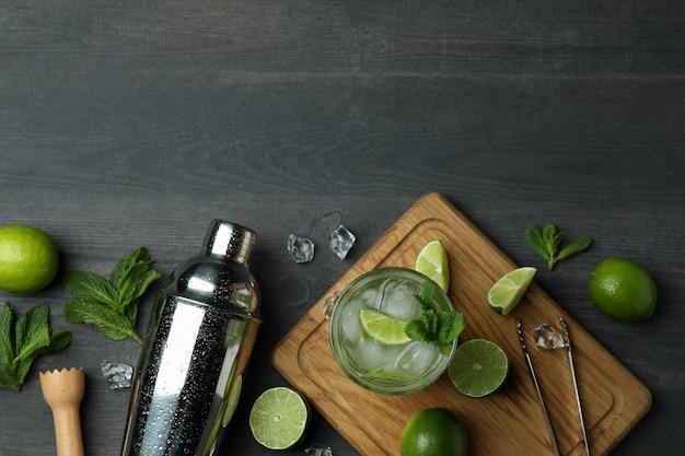 Verre de cocktail mojito, ingrédients et shaker sur fond de bois foncé