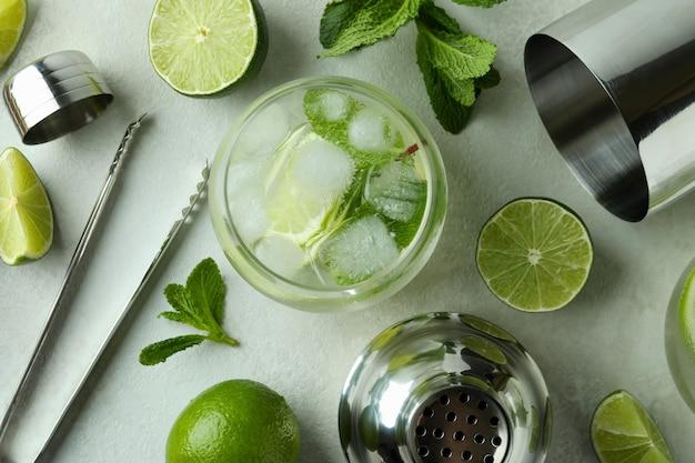 Verre de cocktail mojito et ingrédients sur table texturée blanche
