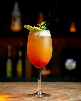 Un verre de cocktail d'orange garni de tranches de menthe et de pomme verte