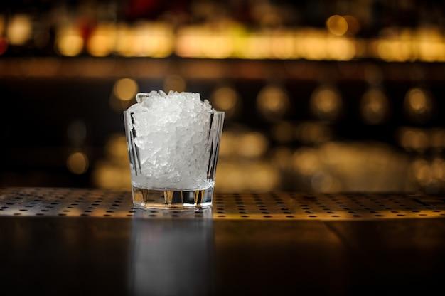 Verre à cocktail orné de glace pilée debout sur le support de bar en acier vide