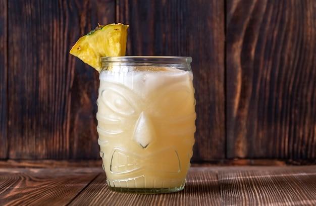 Verre de cocktail painkiller sur table en bois