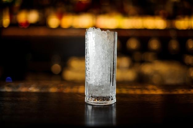 Verre à cocktail à paroi épaisse de glace pilée debout sur le support de bar en acier vide