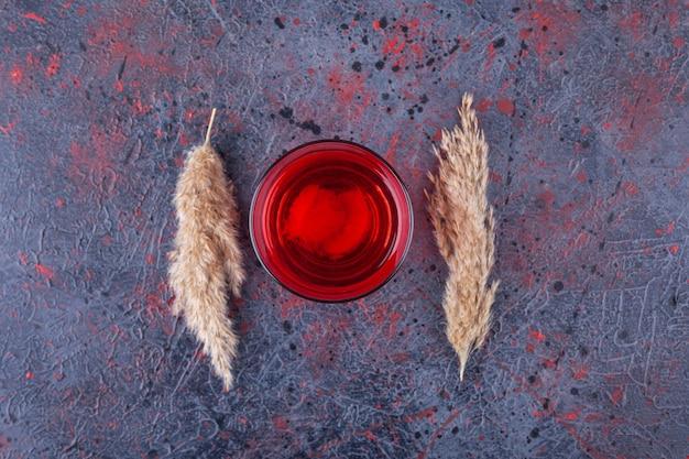 Verre de cocktail rouge avec des tranches de fruits sur marbre.