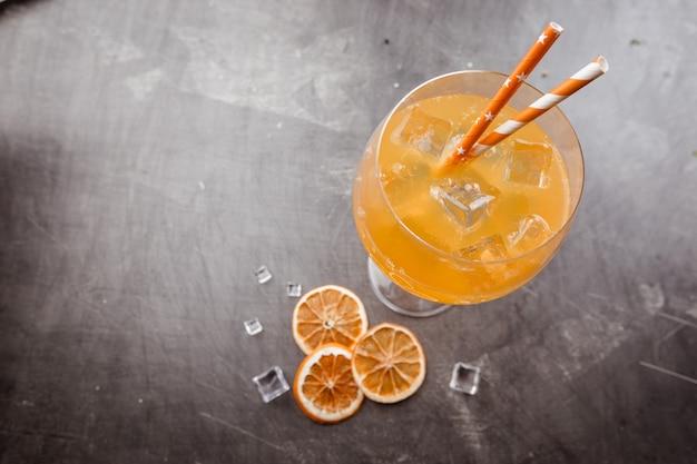 Verre de cocktail soda aperol avec des glaçons sur noir
