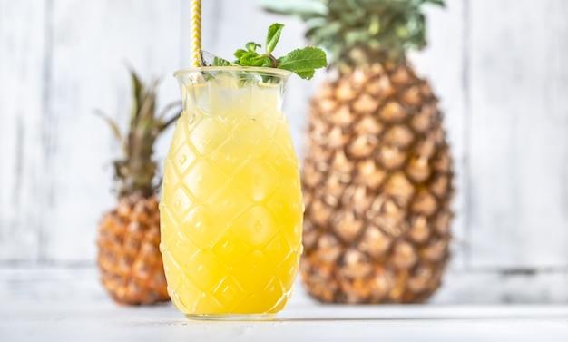 Verre de cocktail de style tiki ananas sur table blanche