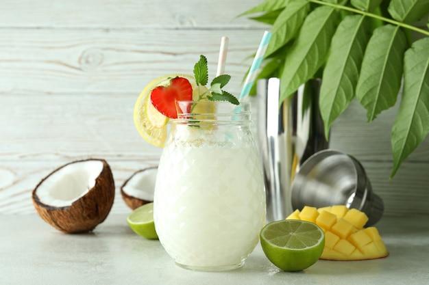 Verre de cocktail tropical et ingrédients sur une table texturée blanche