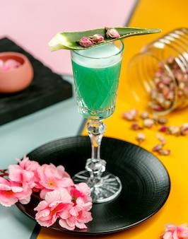 Verre de cocktail vert garni de feuilles d'aloès et de boutons de rose séchés