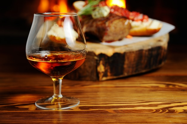 Verre de cognac sur le fond un plat de viande