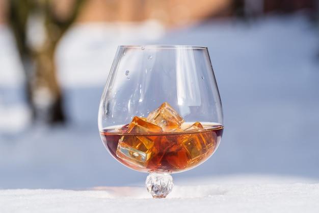 Verre de cognac avec de la glace sur un lit de neige et fond blanc, gros plan