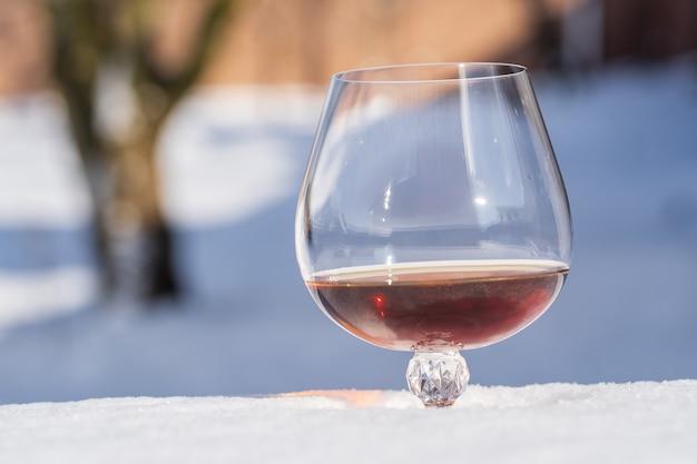 Verre de cognac sur un lit de neige et fond blanc, gros plan. concept de matin d'hiver de noël