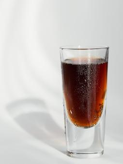 Verre de cola sur fond blanc avec des reflets