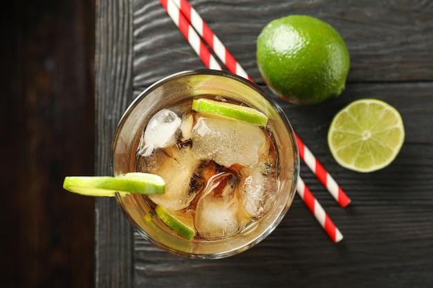 Verre de cola froid avec des agrumes et de la glace sur une table en bois, vue du dessus