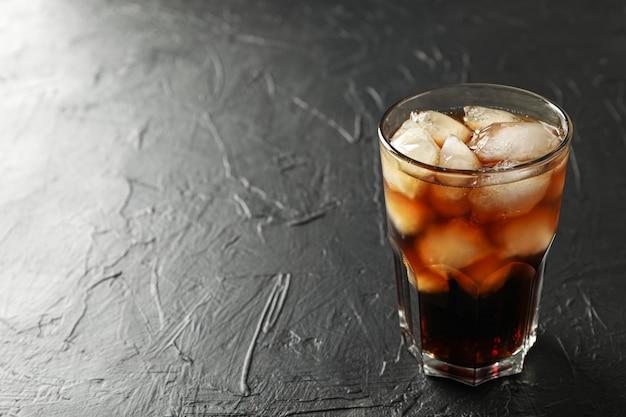 Verre de cola froid sur fond de ciment noir
