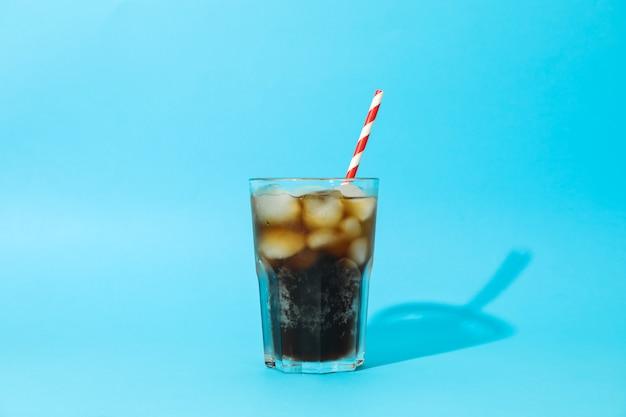 Verre avec cola froid et tubule sur fond bleu, espace pour le texte