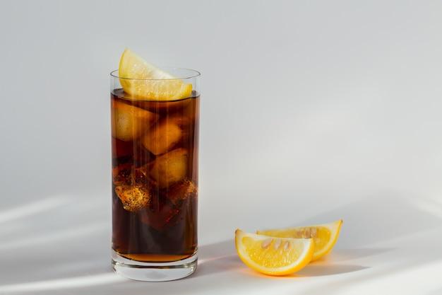 Verre de cola avec de la glace et du citron sur fond blanc