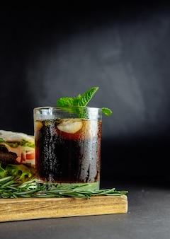 Verre de cola avec de la glace, de la menthe et du romarin sur un gros sandwich noir