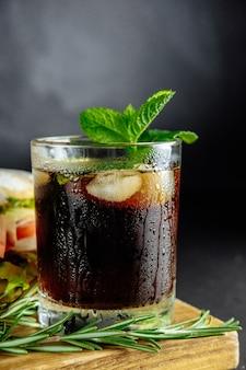 Verre de cola avec glace, menthe et romarin sur gros sandwich noir, nourriture de rue