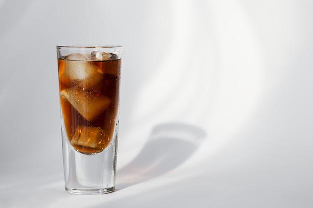 Verre de cola avec de la glace sur un mur blanc