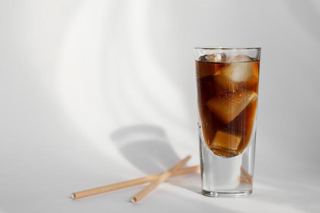 Verre de cola avec de la glace et de la paille sur un mur blanc