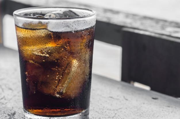 Verre de cola avec glace sur table en bois