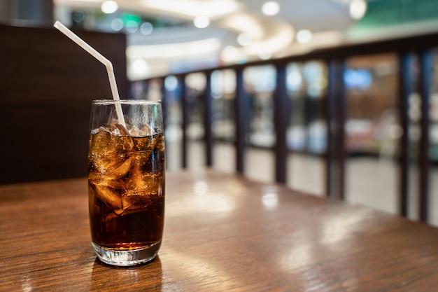 Un verre de cola avec glaçon sur une table en bois sur fond de restaurant floue