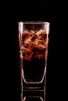 Verre de cola avec des glaçons et des gouttelettes, isolé et avec un tracé de détourage