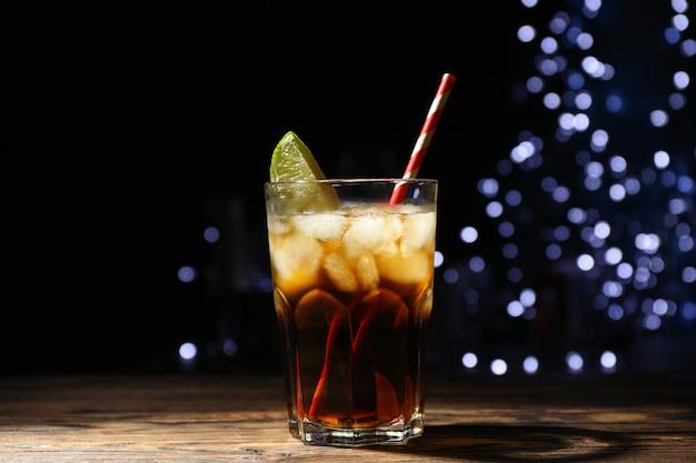 Verre avec cola, tranche de citron vert et tubule sur fond de lumières floues