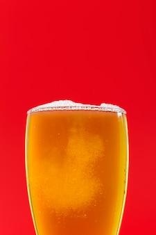 Verre de copie avec de la bière ayant de la mousse