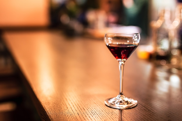 Un verre de coupe avec du vin de porto rouge au comptoir du bar. une photo de style de vie horizontale avec une faible profondeur de champ et un espace de copie.