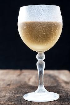 Verre en cristal au vin blanc servi très froid, sur une table rustique avec fond noir.