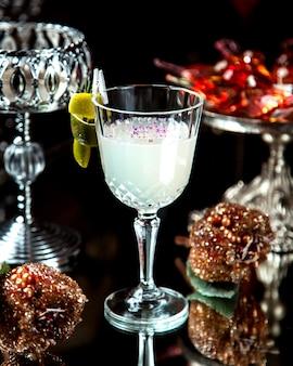 Un verre en cristal avec un cocktail blanc garni de zeste de citron
